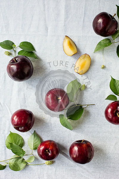 Plums with leaves over white table