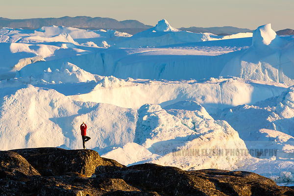 Lone man performing a yoga pose in front of the breathtaking views of the Ilulissat Icefjord in Greenland