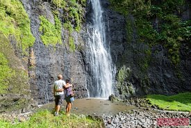 Tourist couple in front of waterfall, Tahiti, French Polynesia