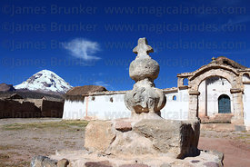 Stone cross and cairn in front of Tomarapi church, Sajama volcano behind, Sajama National Park, Bolivia