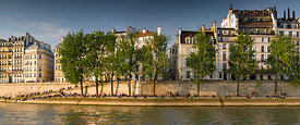 Parisians basking in the sun in the banks of the Seine, at Ile Saint-Louis
