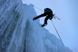 Ice climber rappeling down icefall