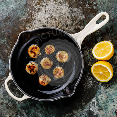 Fried scallops with butter in cast-iron cooking pan with lemon