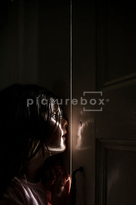 A little girl looking through the gap of a window shutter, with daylight coming in.