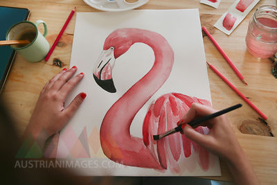 Woman's hand painting aquarelle of a flamingo on desk in her studio