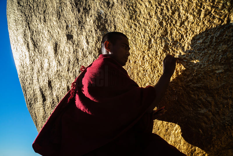 Monk Applying Gold Leaf to the Golden Rock (Kyaikhtiyo)