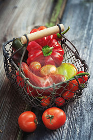 Home-grown sweet peppers and tomatoes on a wooden background