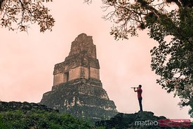 Local man playing a flute in front of mayan temple, Tikal, Guatemala