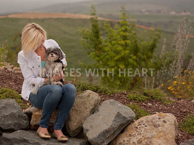 Woman sitting outside with a dog in her lap.