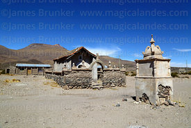 Rustic cairn and church in Churacari village, part of Tunupa volcano in background, Bolivia