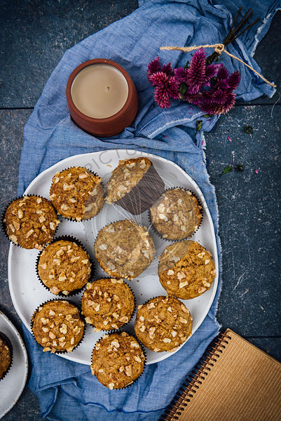 Banana nut muffins served on a large white ceramic plate photographed from top view. A cup of coffee, flowers, a notebook accompany.