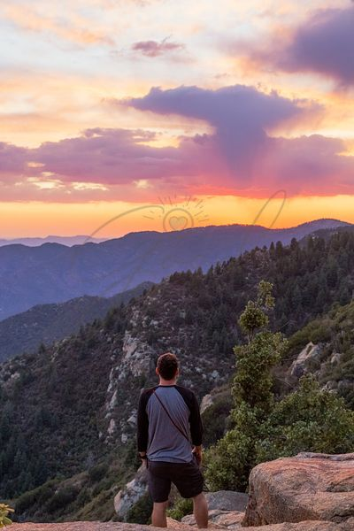 Man Looking at Sunset Over Mountain Range