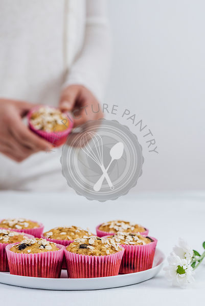 A woman in white clothes removing a pumpkin muffin from a pink muffin liner photographed from front view. A plate full of muffins and white flowers on the table accompany.