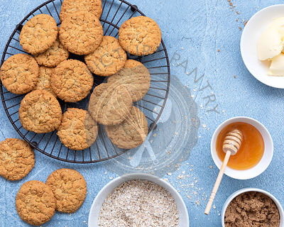 Honey and Oatmeal Biscuits cooling on a wire rack with ingredients.