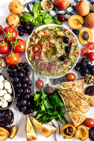 Eggplant babaganoush with red bell pepper and herbs on a snack board full of summer fruit photographed from top view.
