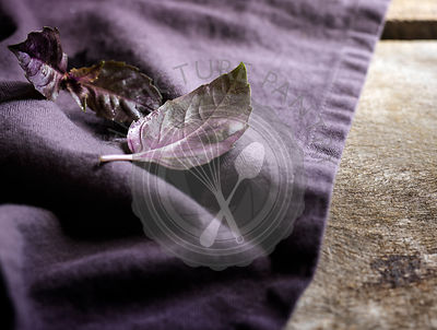 Detail shot of purple basil leaves on a rich purple linen and rustic wood surface.