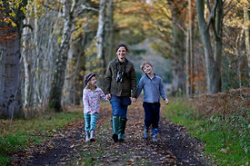Mother, son and daughter on woodland walk in autumn Norfolk