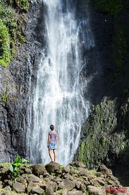 Tourist in front of waterfall, Tahiti, French Polynesia