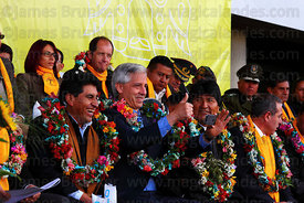 President Evo Morales (right centre) watches as vice president Alvaro Garica Linera (centre) takes a photo of a friend in the crowd with his iphone, El Alto, Bolivia