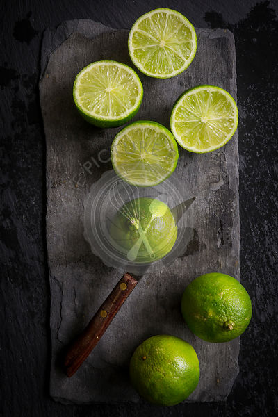 Whole and cut limes on black slate board