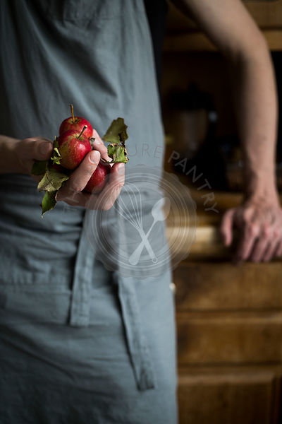 Man with kitchen apron leaning on kitchen cabinet and holding apples in his hand