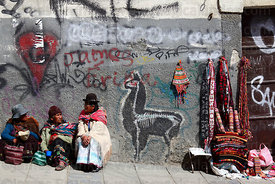 Indigenous women sitting next to textile stall and llama graffiti / street art in street , La Paz , Bolivia