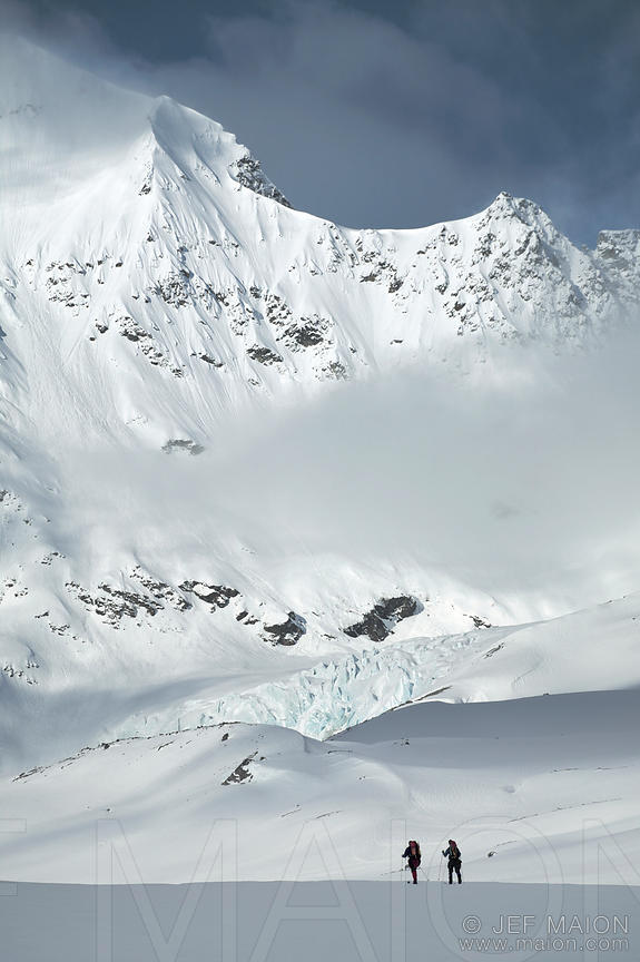 Skiers by mountain face and glacier