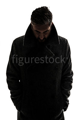 A silhouette of a mystery man in a big coat, looking down – shot from eye level.