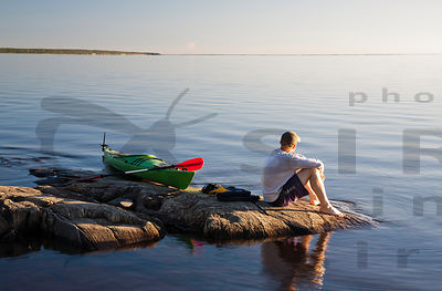 Paddler enjoying the sunset in Oulujärvi, National Hiking Area & part of Rokua Geopark