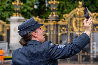 RAF airwoman with wet uniform after being sprayed by the flowerbed sprinklers by Canada Gate