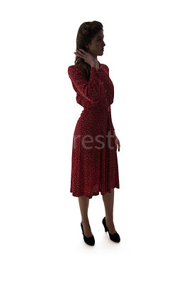 A 1940's woman in a red dress – shot from eye-level.A semi-silhouette of a 1940's woman in a red dress playing with her hair – shot from eye-level.