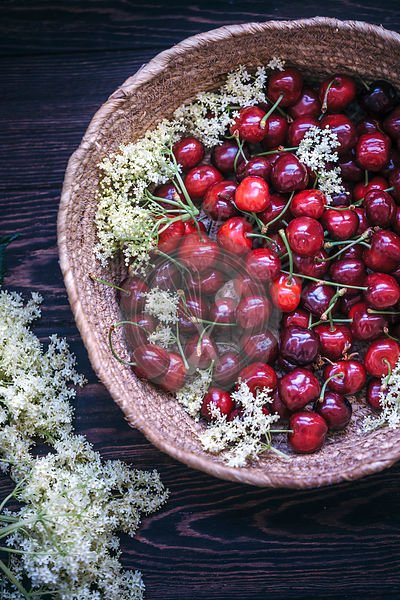 Fresh cherries and flowers in a basket on rustic wooden table