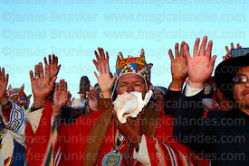 Aymara shamans or amautas hold up their hands to receive the sun's energy at sunrise during Aymara New Year celebrations, Tiwanaku, Bolivia