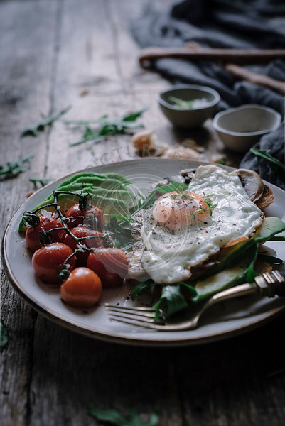 Egg and sliced avocado on toast, set on a rustic kitchen table