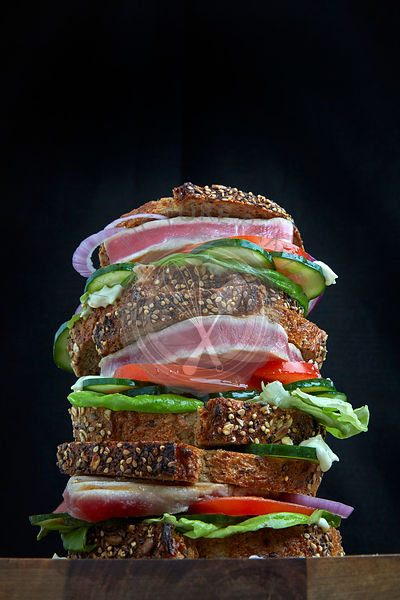 Fresh Tuna Steak Sandwich stacked with lettuce, tomato and cucumber on sliced artisan bread.