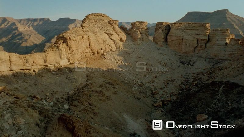 Aerial close up shot up side of mountain to rocky formations at top, over and down to water in river in valley with mountain peaks in background Fish River Canyon Namibia