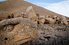 The west terrace of Mount Nemrut with heads of the colossal statues and the tumulus.  Head of guardian eagle in foreground with Antiochos I and Commagene behind.  The UNESCO World Heritage Site at Mount Nemrut where King Antiochus of Commagene is reputedly entombed.  (Turkish: Nemrut Dağı)