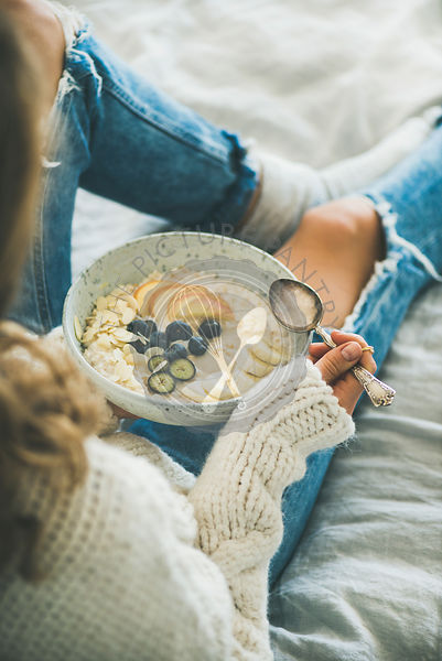 Woman in shabby jeans and sweater eating vegan breakfast