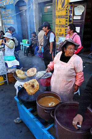 Woman preparing buñuelos, typically served with api or tojorín , La Paz , Bolivia