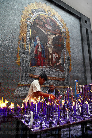 Men arranging candle offerings to Señor de los Milagros mosaic in courtyard behind Las Nazarenas church, Lima, Peru