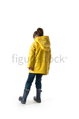 A little girl in wellies and a raincoat playing – shot from mid level.