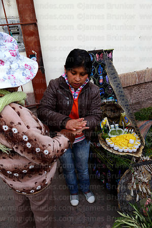 Girl demonstrating snake fat as traditional cure for muscle cramps and pains, Cusco, Peru