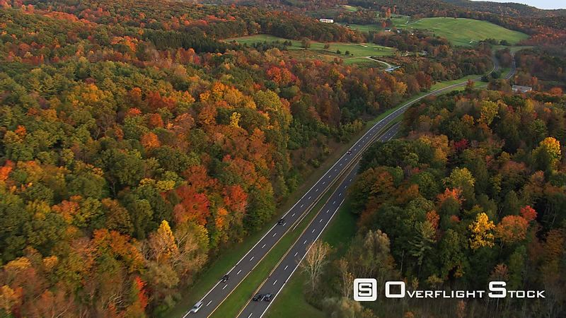 Flying above curving road through New York countryside