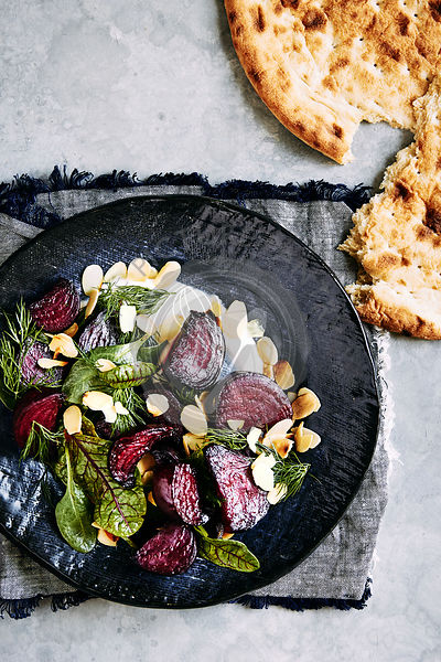 roasted beetroot salad with yogurt dressing, dill, spinage and toasted almonds. topped off with flat bread.