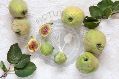 wild quinces and figs, with quince leaves on cream textured background