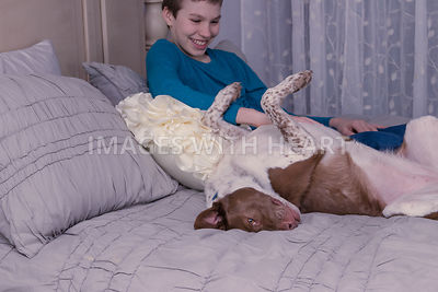 Laughing boy with upside down dog on bed