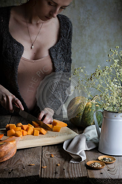A woman chopping pumpkins on wooden rustic table