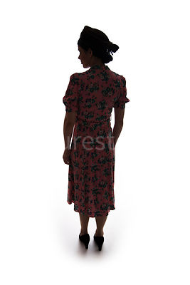 A silhouette of a 1940's woman in a dress and hat – shot from eye-level.