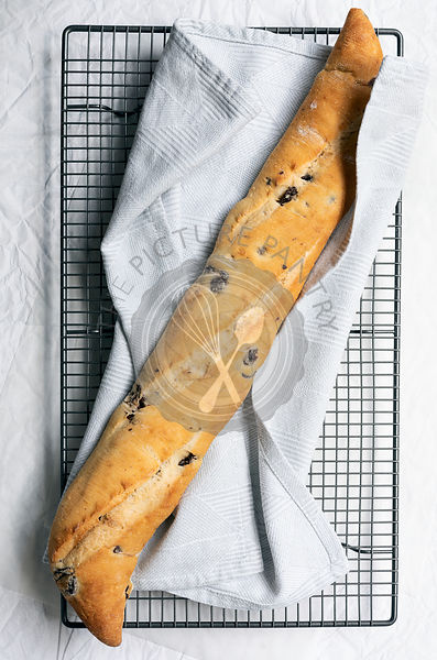 A crusty olive baguette cooling on a wire rack.