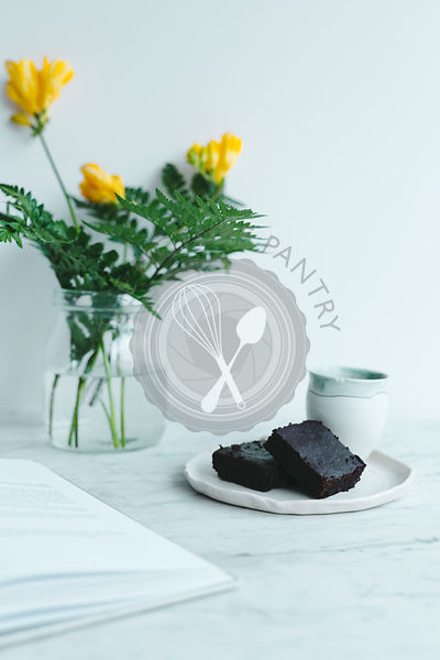 Brownies and flowers with book on marble